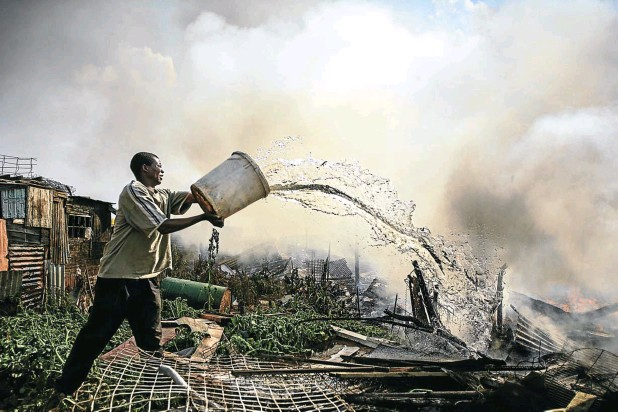 ?? Picture: Alon Skuy ?? A resident of the Ramaphosa informal settlement in Ekurhuleni, east of Johannesburg, fights the flames engulfing a shack in 2008. Tens of thousands fled their homes and hundreds of shops were looted.