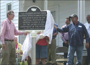 ?? Staff photo/Corey Maxwell ?? Keith Fledderjohann (left) and Wayne Fledderjohann remove the sheet covering the National Heritage Marker that showcases three buildings of the Fledderjohann property that are part of the National Register of Historical Places. The buildings have been on the list since 1993.