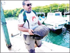 ?? AFP ?? Washington Tapia, a member of Galapagos Conservancy, carries a specimen of the giant Galapagos tortoise Chelonoidis phantasticus, thought to have gone extinct about a century ago.