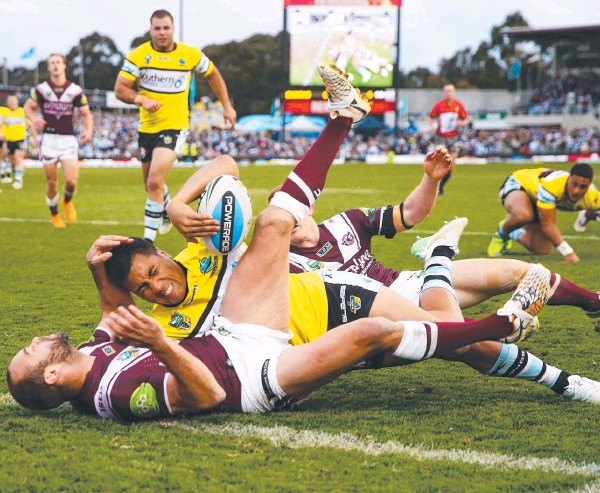 ??  ?? SO CLOSE: Manly fullback Brett Stewart denies Sosaia Feki a try at Remondis Stadium as the Sharks' top-four hopes are dashed. Picture: Getty Images