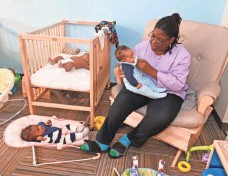 ??  ?? Dionne Bailey, a teacher in the Burke Early Education Center, cares for infants at the COA Goldin Center. Milwaukee foundations and agencies have singled out a handful of communities that especially need their resources, such as the Amani neighborhood.