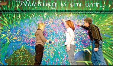 ??  ?? Victoria College of Art and Design students have just completed a mural commissioned for the new nursing facility opening at University Canada West next month. The colourful piece is a blown-up rendition of a stem cell. Left to right are Caitlin...