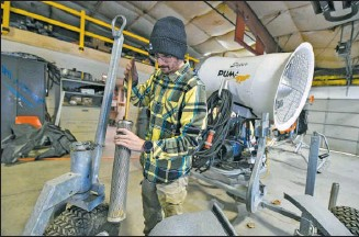 ?? JASON FARMER / STAFF PHOTOGRAPHER ?? Adam Adelman, snowmaking supervisor at Montage Mountain, cleans out a water filter to a snow gun in preparation for blowing snow this week.