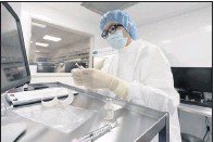 ??  ?? A pharmacist labels syringes in a clean room where doses of COVID-19 vaccines will be handled at Mount Sinai Queens hospital in NewYork. The hospital expects to receive doses once a vaccine gets the green light by U.S. regulators.