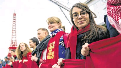 ?? PHOTOGRAPH: JOSE RODRIGUEZ/EPA ?? Holding the red line: A long red sheet is held at a demonstration calling on leaders to take action in Le Bourget, north of Paris.