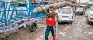 ?? Associated Press ?? Showkat Ahmed carries an empty oxygen cylinder to get it refilled at a gas supplier facility in Srinagar, Kashmir, on Tuesday.