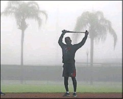 ?? Curtis Compton/Atlanta Journal-Constitution ?? Ron Washington, the Atlanta Braves' third-base coach and a former Rangers manager, stretches in the dense morning fog before workouts in Lake Buena Vista, Fla.
