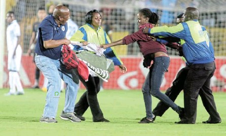 ?? /ANTONIO MUCHAVE ?? George Mogotsi, left, in the thick of things trying to keep order after a #FeesMustFall protester had run onto the pitch during a match at Bidvest Stadium.