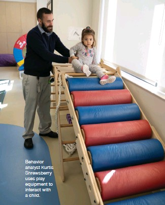 ??  ?? Behavior analyst Kurtis Shrewsberry uses play equipment to interact with a child.