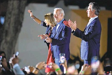 ?? Wally Skalij Los Angeles Times ?? PRESIDENT BIDEN walks onstage with Gov. Gavin Newsom and his wife, Jennifer Siebel Newsom, on Monday at Long Beach City College. Biden's stop in California marked the closing campaign act for the governor.