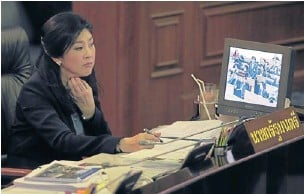 ?? THITI WANNAMONTHA ?? Prime Minister Yingluck Shinawatra looks at a computer monitor on which opposition leader Abhisit Vejjajiva is shown criticising the government's performance during its first year in office. The government yesterday delivered its first-year performance...