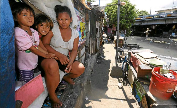 ?? RAFFY LERMA ?? LIVING ONTHE EDGE Janet Francisco, 25, with children Melody, 6, and Rose Jane, 7, living near the Paco-Pandacan Bridge in Manila. They used to live under the bridge.
