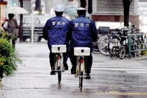 ??  ?? POLICE ride bicycles on the street under heavy rain in Tokyo on Oct. 29, 2017