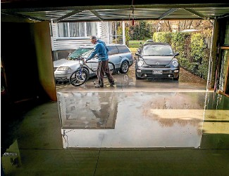 ?? PHOTO: JOHN KIRK-ANDERSON/STUFF ?? Chris Benn cleans bikes at his Eastern Tce home in Christchurch. His two cars were flooded.