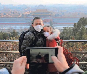 ?? WU HONG/EPA-EFE ?? People wear masks posing for photos while the Forbidden City, seen from a viewing deck of Jingshan Park in Beijing, China, is closed.