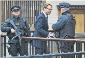 ??  ?? Tobias Ellwood, the MP who helped treat Pc Keith Palmer, shakes hands with an officer, yesterday, as a street leading to the Houses of Parliament was blocked by Jankel 'Guardian' vans, top