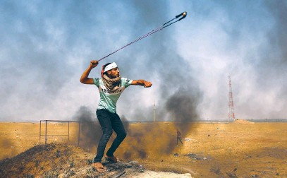 ?? Picture: AFP ?? ROCKS AND ROCKETS. A Palestinian demonstrator hurls rocks with a slingshot next to burning tyres during a protest by the border with Israel, east of Rafah in the southern Gaza Strip on Monday.