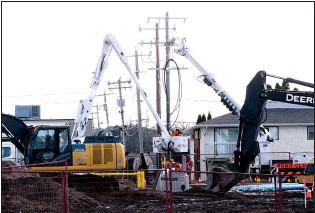 ?? NEWS PHOTO COLLIN GALLANT ?? Work crews move utility lines near the site of a new car wash at the intersection of Dunmore Road and 22nd Street in Medicine Hat in early November.