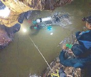 ?? AFP ?? A team of Royal Thai Navy SEAL divers inspect the water-filled tunnel in the Tham Luang cave on Thursday during a rescue operation for the 12 missing children and their coach in Chiang Rai province.