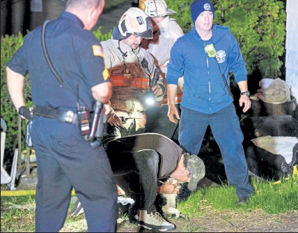 ?? DAVID BRYCE / SENTINEL & ENTERPRISE ?? A frantic effort was made to save a pet cat that was pulled from the Lancaster apartment house at 217 White Pond Road Tuesday night. Despite the efforts, the cat died. None of the residents of the apartments was injured in the fire.