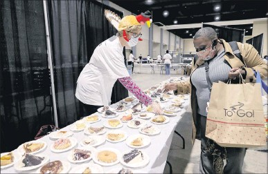 ?? DANIEL SANGJIB MIN/ TIMES-DISPATCH ?? Jenni Brockman (left), a volunteer, handed out desserts at The Giving Heart's Community Thanksgiving Feast, which took place Thursday at the Greater Richmond Convention Center. Organizers had the ability to feed a little more than 3,000.