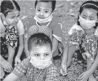 ??  ?? Cuatro niños asisten a un funeral en Rangún, Birmania.