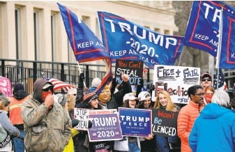 ?? Jeff Kowalsky / AFP via Getty Images ?? Supporters of President Trump gather in Lansing, Mich., where the Board of State Canvassers heard public comments before certifying the election victory of Presidentelect Joe Biden.