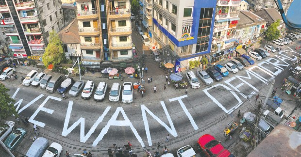 ?? REUTERS ?? words decrying the feb. 1 military coup in Myanmar are seen on a street in the city of Yangon on sunday. the killings of two protesters saturday have further stoked pro-democracy demonstrations in the country.