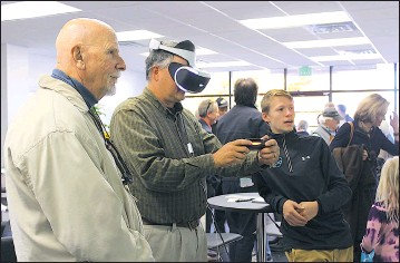 ?? FILE PHOTO ?? Chestertown Mayor Chris Cerino, center, takes a turn at experiencing a virtual reality game while Chestertown Councilman Marty Stetson and Franklin Wagner look on during ThinkBig Networks' open house Nov. 18, 2016 at its new office in Chestertown.