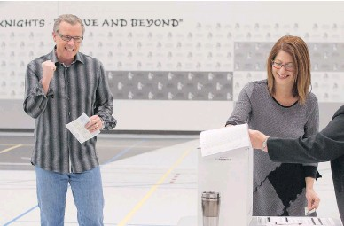 ?? MICHAEL BELL / THE CANADIAN PRESS ?? Saskatchewan Party Leader Brad Wall celebrates his wife Tami's vote Monday in Swift Current. Wall's party won its third straight mandate, posting an overwhelming majority in the provincial election.