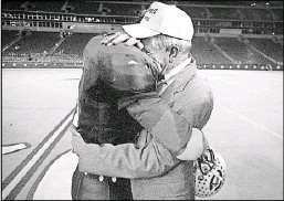 ?? File Photo/Staff ?? Moore, then Celina's quarterback, embraced his father, head coach G.A. Moore, after Celina won the 1995 Class 2A state football championship.