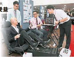 """??  ?? 王建民(左一)向""""创新大马卓越大奖""""得主队员陈伟颋(右起)、温振良及颜峥宏了解他们的得奖创作""""中风康复系统""""的操作方式。"""