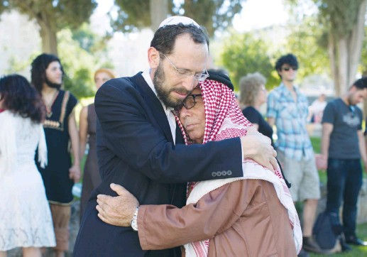 ?? (Sarah Schuman/Flash90) ?? RABBI YAKOV NAGEN of Otniel embraces Haj Ibrahim Ahmad Abu el-Hawa of Jerusalem during an event called The Big Hug, in 2013.