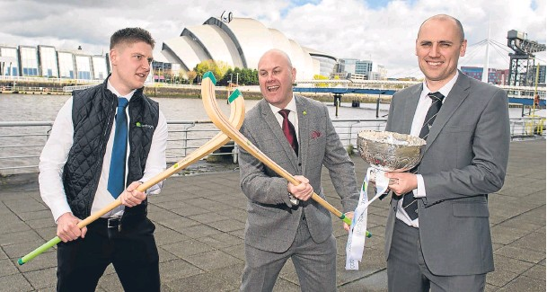 ??  ?? QUICK ON THE DRAW: Stuart Walken and Mark Whitehouse, of tournament sponsor cottages.com, cross camans, while the Camanachd Association's Derek Keir holds the silverware at yesterday's MacTavish Cup draw at Pacific Quay, Glasgow