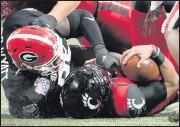 ?? THE ASSOCIATED PRESS ?? Georgia defensive lineman DevonteWyatt tackles Cincinnati quarterback Desmond Ridder during the second half of the Bulldogs' win in the Peach Bowl.