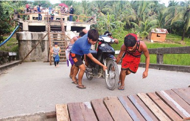 ??  ?? RESILIENCE – These boys pull a motorbike up an incline created by the collapse of the Anao-aon Bridge in San Francisco, Surigao del Norte as other residents take a wooden stairway in the aftermath of a 6.5-magnitude earthquake that devastated the area...
