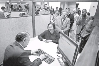 ?? FILE PHOTO BY JUSTIN SULLIVAN, GETTY IMAGES ?? Oakland Mayor Jean Quan, seated, registers for a municipal identification card on Feb. 1, 2013, after Oakland became the first city to offer such IDs to undocumented immigrants.
