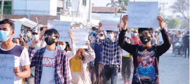 ?? Agence France-presse ?? ↑ Protesters hold placards as they march during a demonstration against the military coup in Mandalay on Tuesday.