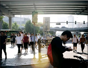 ?? Bloomberg photo by Giulia Marchi ?? A cyclist looks at his smartphone as pedestrians walk on a sidewalk in the central business district in Beijing on June 1, 2018.