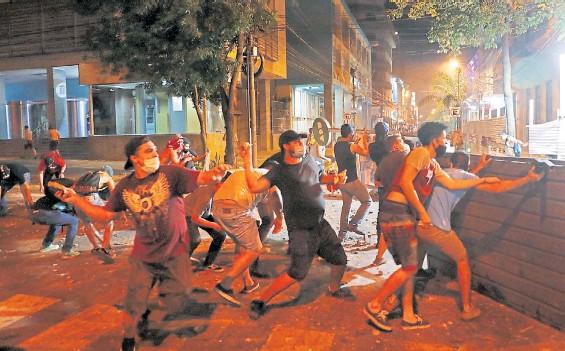 ??  ?? Enfrentamiento. Los manifestantes más violentos arrojan piedras contra la policía antidisturbios durante la manifestación en Asunción.AFP
