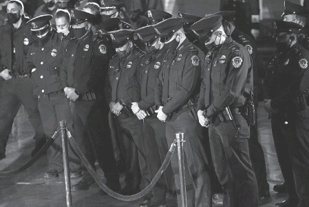 ?? POOL PHOTO BY ERIN SCHAFF ?? U. S. Capitol Police officers pay their respects to fellow officer Brian Sicknick as he lies in honor in the Capitol Rotunda on Feb. 2. Sicknick, 42, died in a hospital the day after a mob stormed the building.