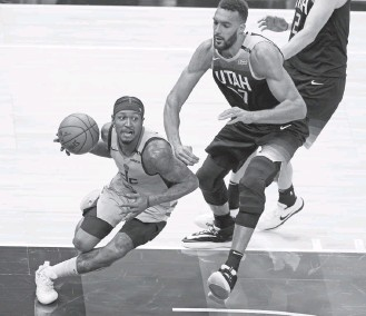 ?? RICK BOWMER/ASSOCIATED PRESS ?? Bradley Beal, driving around Jazz center Rudy Gobert, led the Wizards with 34 points in 37 minutes.