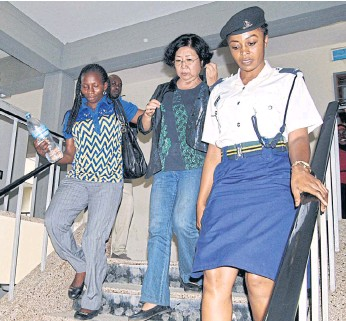 ??  ?? HELD: Yang Feng Glan, centre, who is suspected of trafficking ivory, is escorted by police officers as she leaves the Kisutu Residents Magistrate Court in Dar es Salaam, Tanzania, in October.