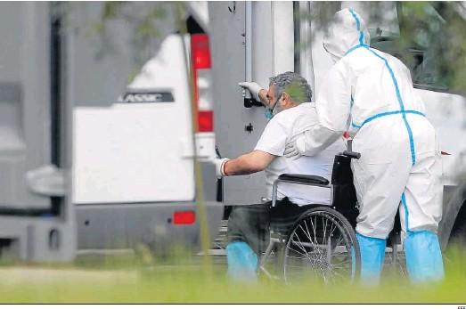 ?? EFE ?? Un sanitario traslada a un paciente en una silla de ruedas.