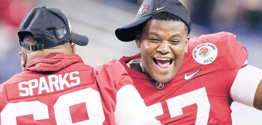 ?? RONALD MARTINEZ/GETTY ?? Alabama's Javion Cohen, right, celebrates with teammates after the Crimson Tide defeated Notre Dame 31-14 in a College Football Playoff semifinal at the Rose Bowl Game on Friday in Arlington, Texas.