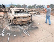 ?? JOSH EDELSON, AFP/GETTY IMAGES ?? James Hough photographs a relative's new car after the Valley Fire roared through the area near Middletown.