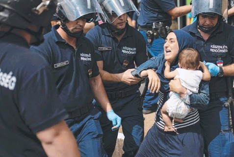 ??  ?? BLOCKED: A migrant woman is arrested after her train from Budapest was stopped en route to Austria. Picture: AFP