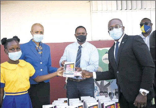 ??  ?? TABLET TIME From left, student of Moore's Primary School, Tressan Grant; Minister of Education, Youth And Information Fayval Williams; community liaison officer of New Fortress Energy, Joel Campbell; and Member of Parliament of South East Clarendon, Pearnel Charles Jr pose for a photo oppurtunity.