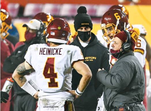 ?? JONATHAN NEWTON/THE WASHINGTON POST ?? Quarterback Alex Smith, center, could only watch from the sideline as Taylor Heinicke filled in during Washington's playoff loss to Tampa Bay on Saturday night.