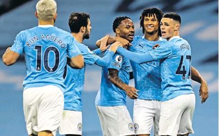 ?? MICHAEL REGAN/EPA ?? Sterling felicitado pelos seus colegas do City após ter marcado o golo do triunfo sobre o Arsenal